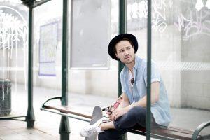 jeune homme attend à l'arrêt de bus sur son téléphone